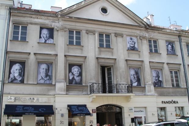 Warszawa: okna kamienicy przy Nowym Świecie z portretami seniorów